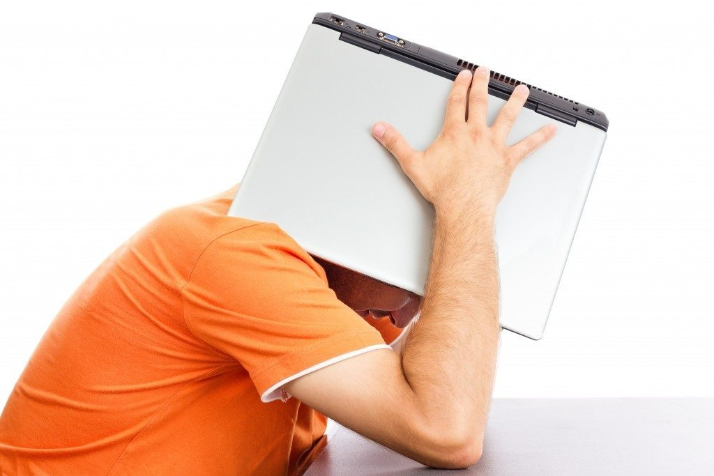 man laptop on head orange shirt