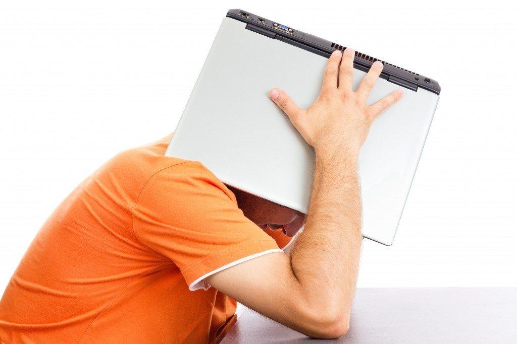 man laptop on head orange shirt