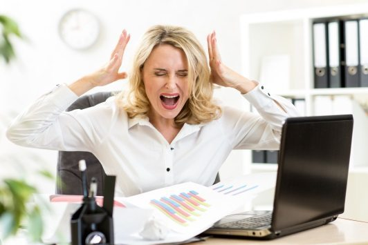 Stressed business woman screaming loudly at laptop in office success without stress raw energy
